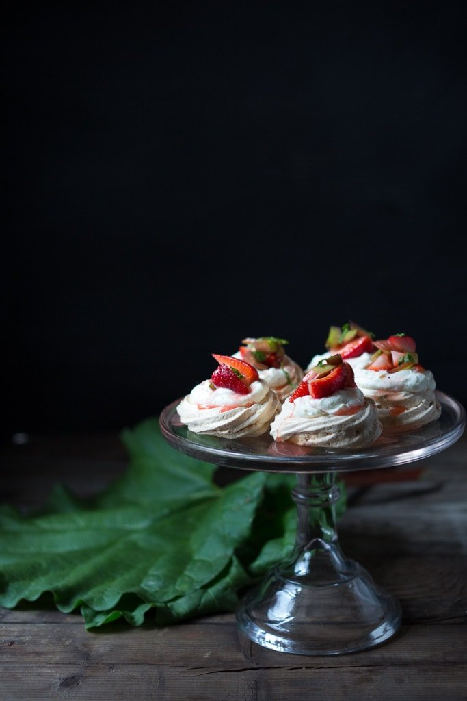 Mini Pavlova Recipe with strawberries, rhubarb and meyer lemon whipped cream! A light and airy dessert idea perfect for celebrations and gatherings. Can be made ahead!  #minipavlova #pavlova #dessert