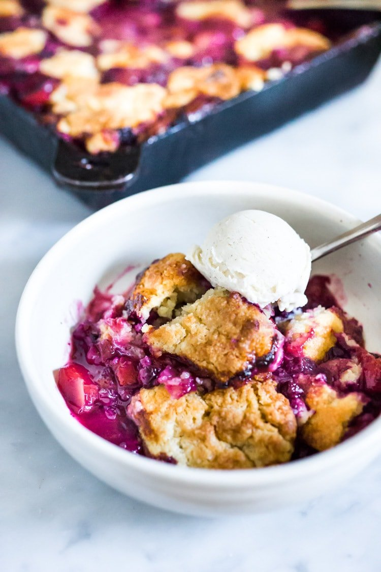 This Peach Skillet Cobbler is topped with a golden and delicious, biscuit topping with fresh summer peaches and berries. This can be made gluten-free and or vegan! #peachcobbler #skilletcobbler #summer #desserts #peachdesserts #huckleberries #vegancobler #glutenfreecobbler #vegandessert