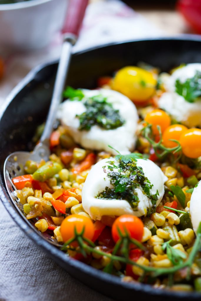 Breakfast Succotash with zucchini, corn and peppers, topped with poached eggs and a flavorful herb oil. | www.feastingathome.com