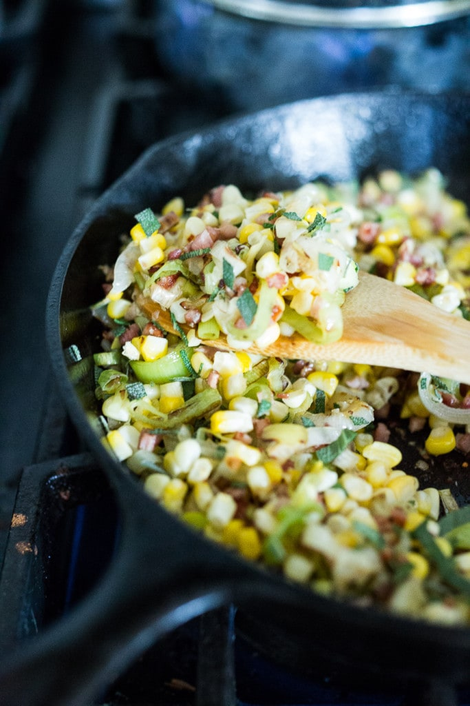"""A simple delicious recipe for Halibut with corn, pancetta and sage, served over a """"lightened-up"""" creamy polenta. And the best part is it can be made un under 30 minutes!   www.feastingathome.com"""