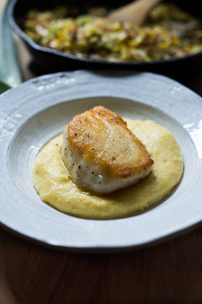 "A simple delicious recipe for Halibut with corn, pancetta and sage, served over a ""lightened-up"" creamy polenta. And the best part is it can be made un under 30 minutes! 