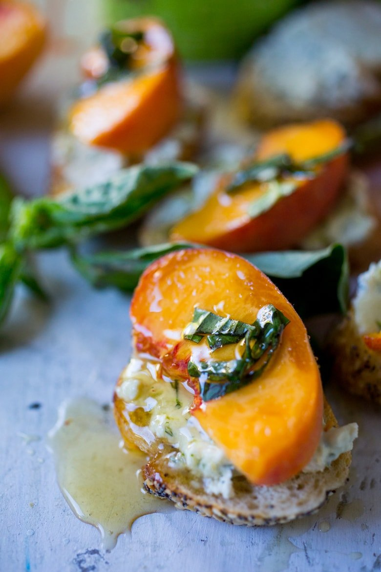 Peach bruschetta with goat cheese, fresh basil and infused honey! A simple way to use fresh summer peaches in a savory way! #peaches #peachappetizer #summerappetizer #peachrecipes