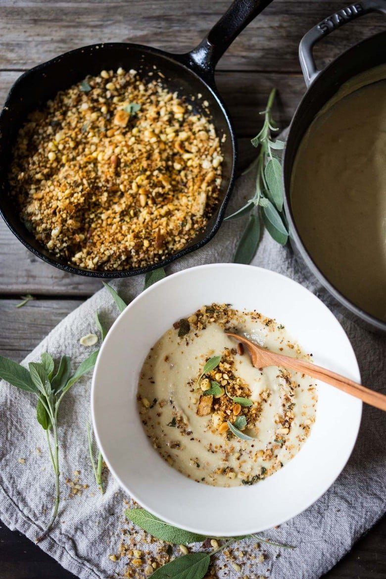 """Creamy Cauliflower Soup with garlic and sage, topped with an optional pine nut""""crumble"""" - healthy, quick and easy, perfect for weeknights when time is short. 