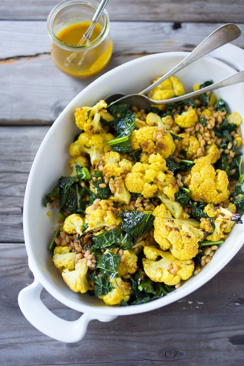 Roasted cauliflower salad with farro, kale and deilcious Turmeric Dressing | PLUS 10 Simple Powerful Turmeric Recipes to Heal, Sooth and Protect | Add fresh turmeric to dressings for a punch of flavor and anti-oxidants | #turmeric #turmericrecipes #cauliflowersalad #caulifower #farro #kale #vegansalad #cleaneating |www.feastingathome.com