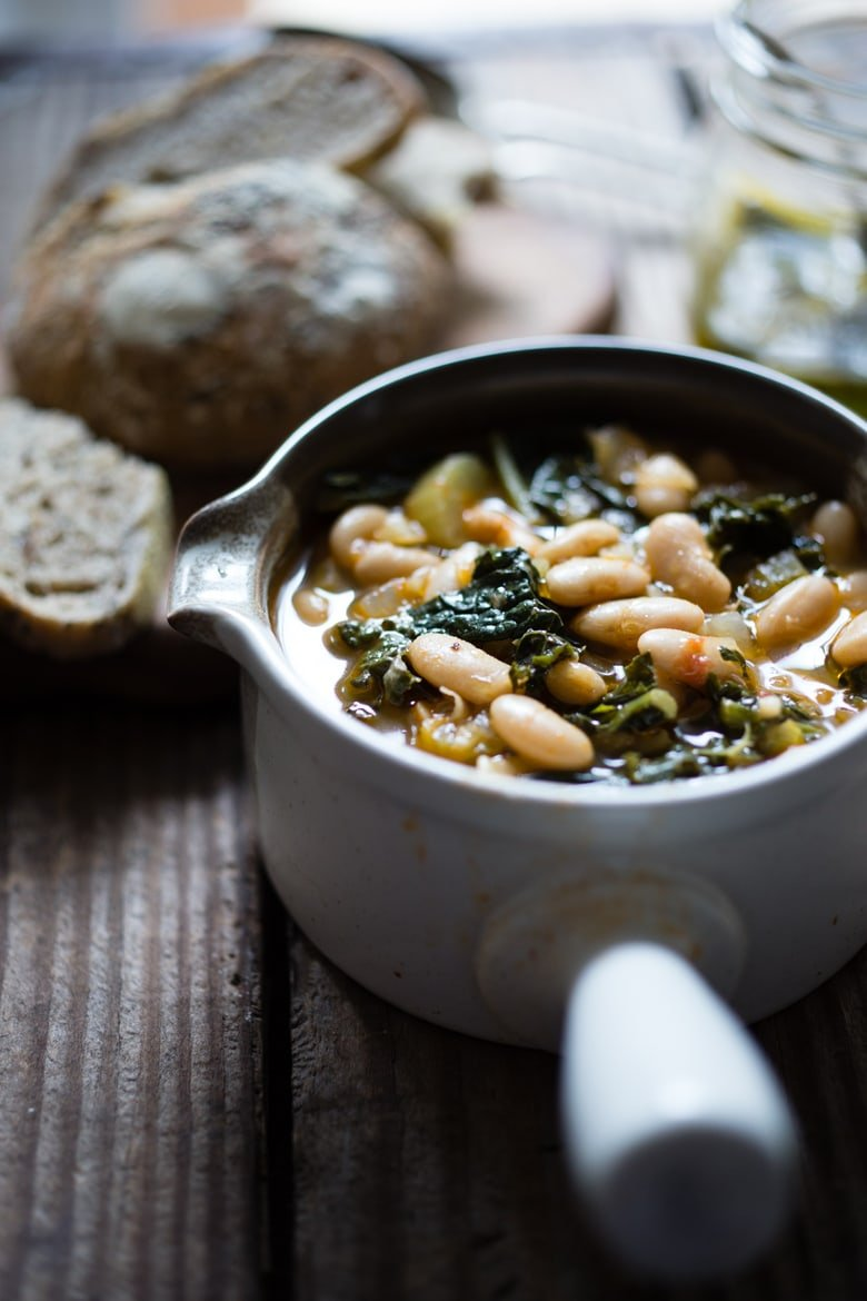 30 Comfort Food Recipes for Fall! A flavorful hearty stew from Tuscany, called Ribollita with Cannellini beans, lacinato kale, and vegetables, served with crusty bread, drizzled with a Lemon Rosemary Garlic Oil.   www.feastingathome.com