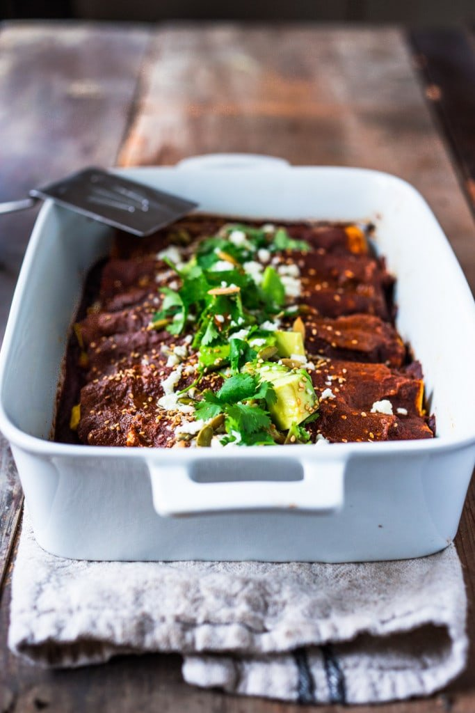 Roasted Butternut Enchiladas with Quick Mole Sauce - topped with cilantro, avocado and toasted sesame and pumpkin seeds. An easy delicious vegetarian main. Vegan-adaptable!| #mole #molesauce #enchiladas #vegetarian #butternut #butternutenchiladas #fallrecipes www.feastingathome.com