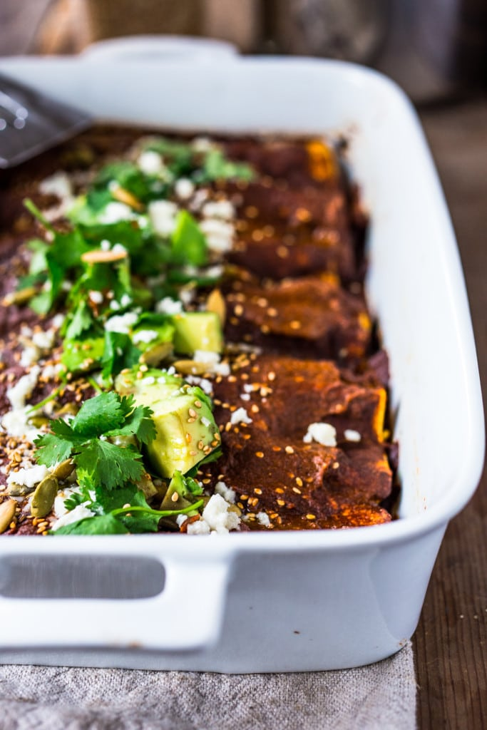 Roasted Butternut Mole Enchiladas with Blackbeans - topped with cilantro, avocado and toasted sesame and pumpkin seeds. An easy delicious vegetarian main.Vegan-adaptable! | www.feastingathome.com