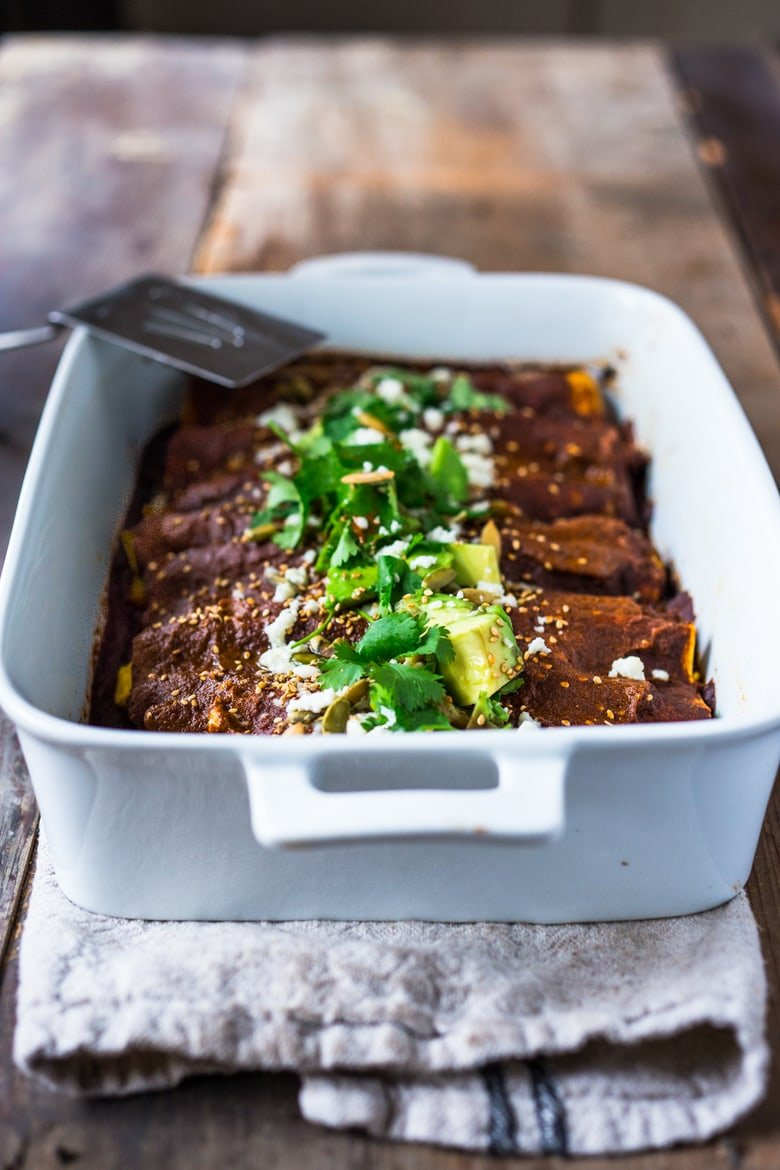 Roasted Butternut Mole Enchiladas with Blackbeans - topped with cilantro, avocado and toasted sesame and pumpkin seeds. An easy delicious vegetarian main.   www.feastingathome.com