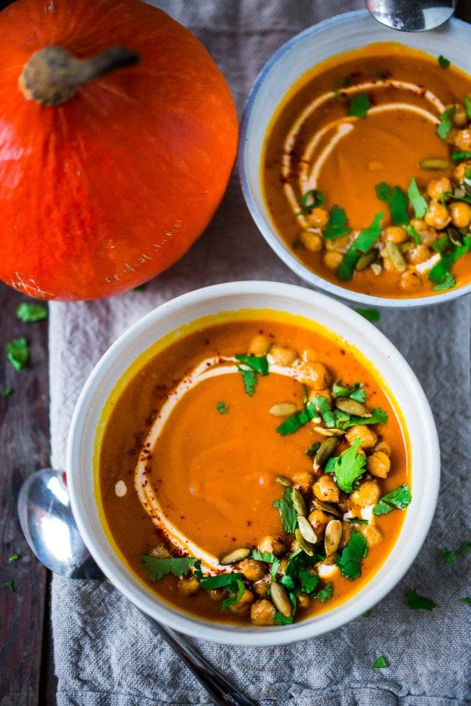Roasted Kuri Squash Soup with Smokey Harissa, roasted crispy chickpeas and toasted pumpkin seeds, swirled with optional yogurt.   #kurisquash #kuri #roastedsquashsoup www.feastingathome.com