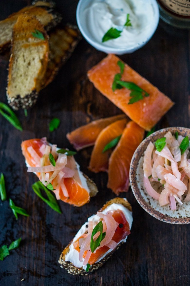 Lox and pickled fennel Bruschetta! This simple recipe for Salt Cured Salmon with rosemary, juniper berries (optional) vodka and lemon zest requires only a few minutes of prep, and then watch as nature takes its course. | www.feastingathome.com
