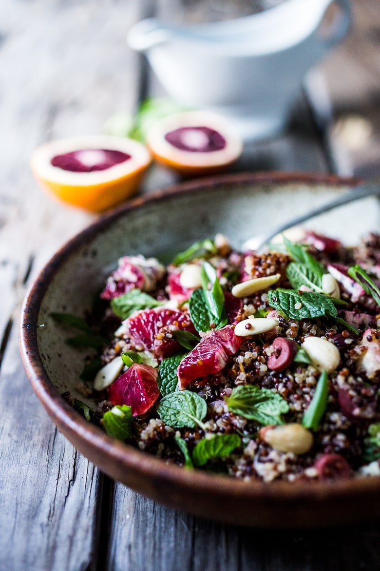 A delicious vegan Moroccan Salad with blood oranges, quinoa, almonds, olives, mint and a tangy, bright blood orange dressing. Perfect for the holiday table, this salad is festive and healthy! | #moroccansalad #bloodorange #bloodorangesalad #quinoasalad #vegansalad #holidaysalad #vegan #healthysalad www.feastingathome.com