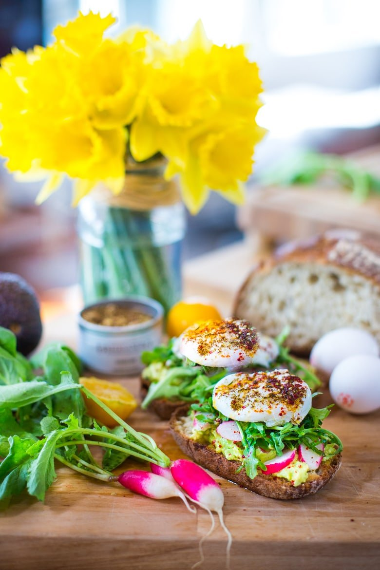 A simple tasty recipe for Avocado Toast with Poached Eggs, arugula, zaatar, lemon and radishes. Quick and delicious ...and healthy! | www.feastingathome.com