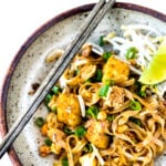 The Best 15 MINUTE PAD THAI- an easy, authentic recipe with made with accessible ingredients that can be made with chicken or tofu! Gluten free, Vegan adaptable with Incredible flavor ! | #authenticpadthai #easypadthai #padthai #padthainoodles www.feastingathome.com