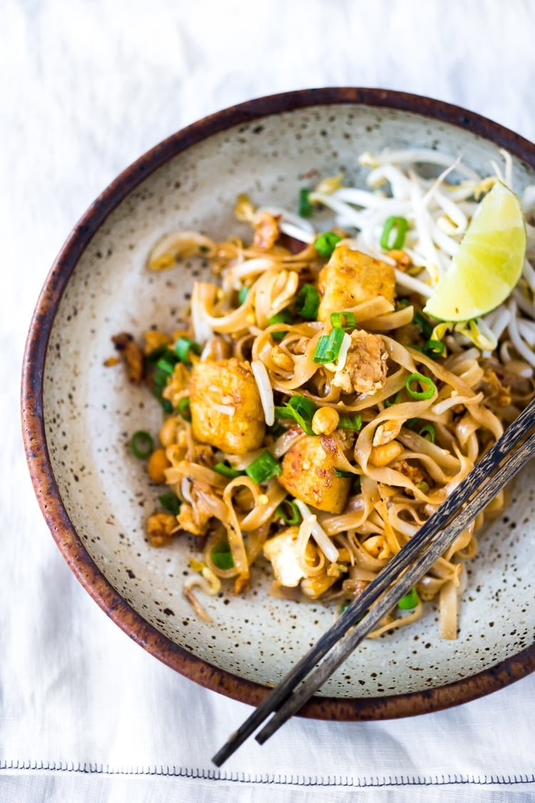 BEST 15 MINUTE PAD THAI- an easy, authentic recipe with made with accessible ingredients that can be made with chicken or tofu! Gluten free, Vegan adaptable with Incredible flavor ! | #authenticpadthai #easypadthai #padthai #padthainoodles www.feastingathome.com