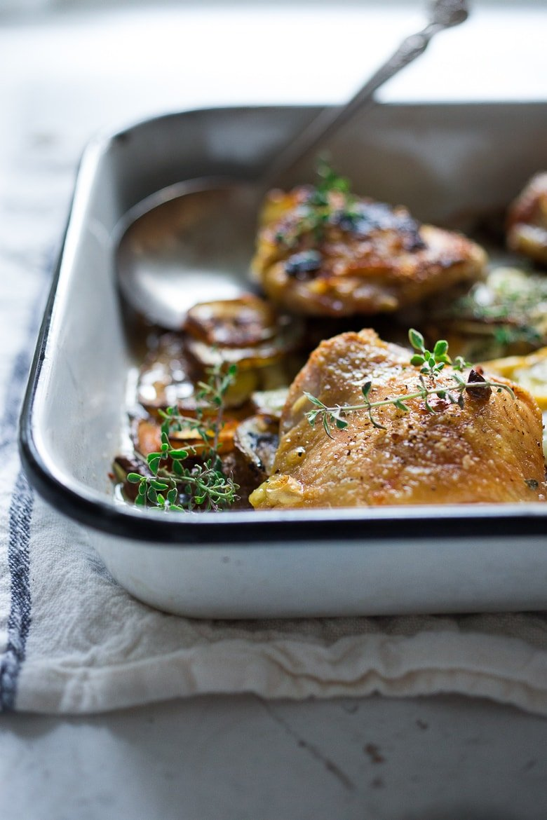 An EASY delicious recipe for One-Pan Chicken and Crispy Potatoes infused with fresh thyme, lemon, and garlic. 10 minutes of prep, then just bake! | www.feastingathome.com