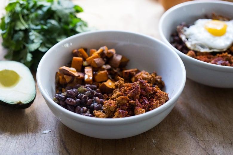 Healthy Yummy Breakfast Bowls with sweet potatoes, blackbeans, turkey chorizo ( optional) avocado, cilantro and and egg. | www.feastingathome.com
