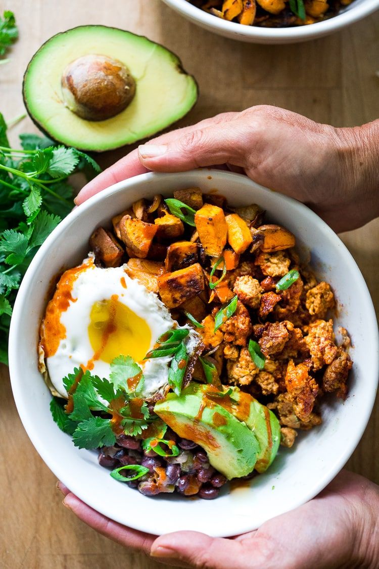 Healthy, delicious Mexican Breakfast Bowls with roasted sweet potatoes, seasoned black beans, homemade turkey chorizo ( optional- or use vegan chorizo) avocado, cilantro and an egg. Easy, Full of flavor and lightened-up! #breakfastbowl #mexicanbreakfastbowl #healthybreakfast #mexicanbreakfast #breakfastbowls