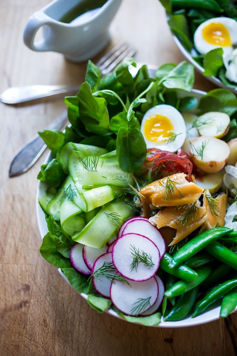 20 Delicious Healthy Lunches! |Nordic Nicoise Salad with smoked salmon on a bed of greens with radish, cucumber baby potatoes, capers, dill, and horseradish-spiked nicoise dressing. #nicoise #salad #smokedsalmon #healthylunch #healhtylunches #smokedtrout www.feastingathome.com