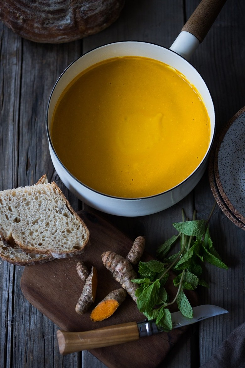 A delicious, healthy recipe for Glowing Carrot Turmeric Soup with Coconut Milk and ginger. Fresh turmeric and mint gives this soup its exotic flavor. Vegan. | www.feastingathome.com