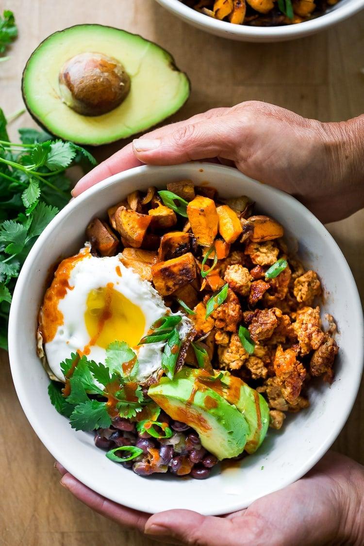 Mexican Breakfast Bowls with sweet potatoes, blackbeans, turkey chorizo (optional) avocado, cilantro and an egg. | www.feastingathome.com