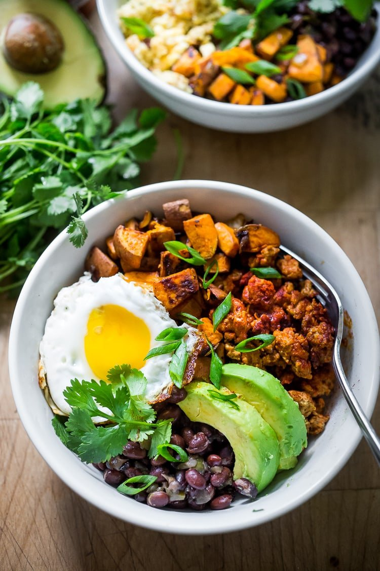 Mexican Breakfast Bowls with sweet potatoes, blackbeans, turkey chorizo (optional) avocado, cilantro and an egg. | #breakfastbowls #turkeychorizo #breakfastbowl www.feastingathome.com