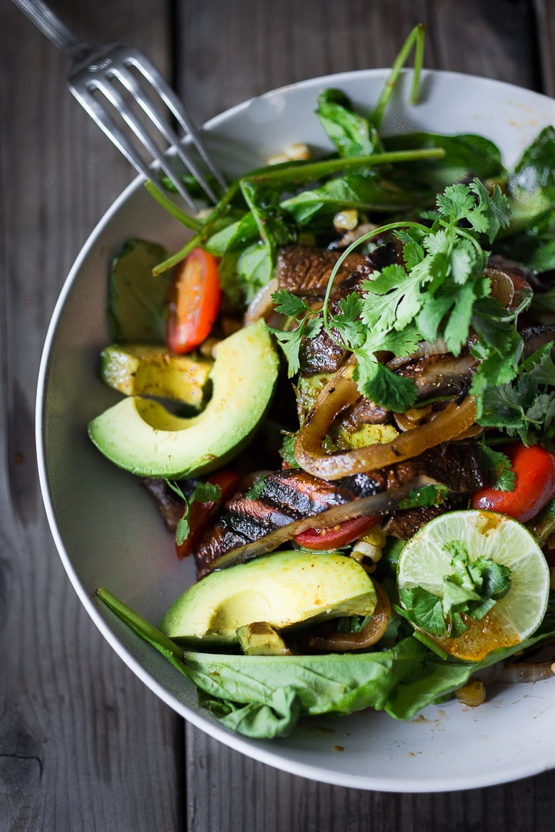 A simple tasty recipe for Grilled Portobello Steak Salad with avocado, lime, grilled sweet onions, grilled corn, tomatoes and a Smokey Lime Dressing. Vegan and Gluten Free! | www.feastingathome.com