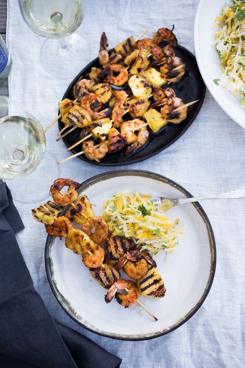 A simple tasty recipe for Grilled Pineapple Chipotle Shrimp Skewers, served with a refreshing Jicama Mango Slaw with cilantro and lime. SO EASY! | www.feastingathome.com