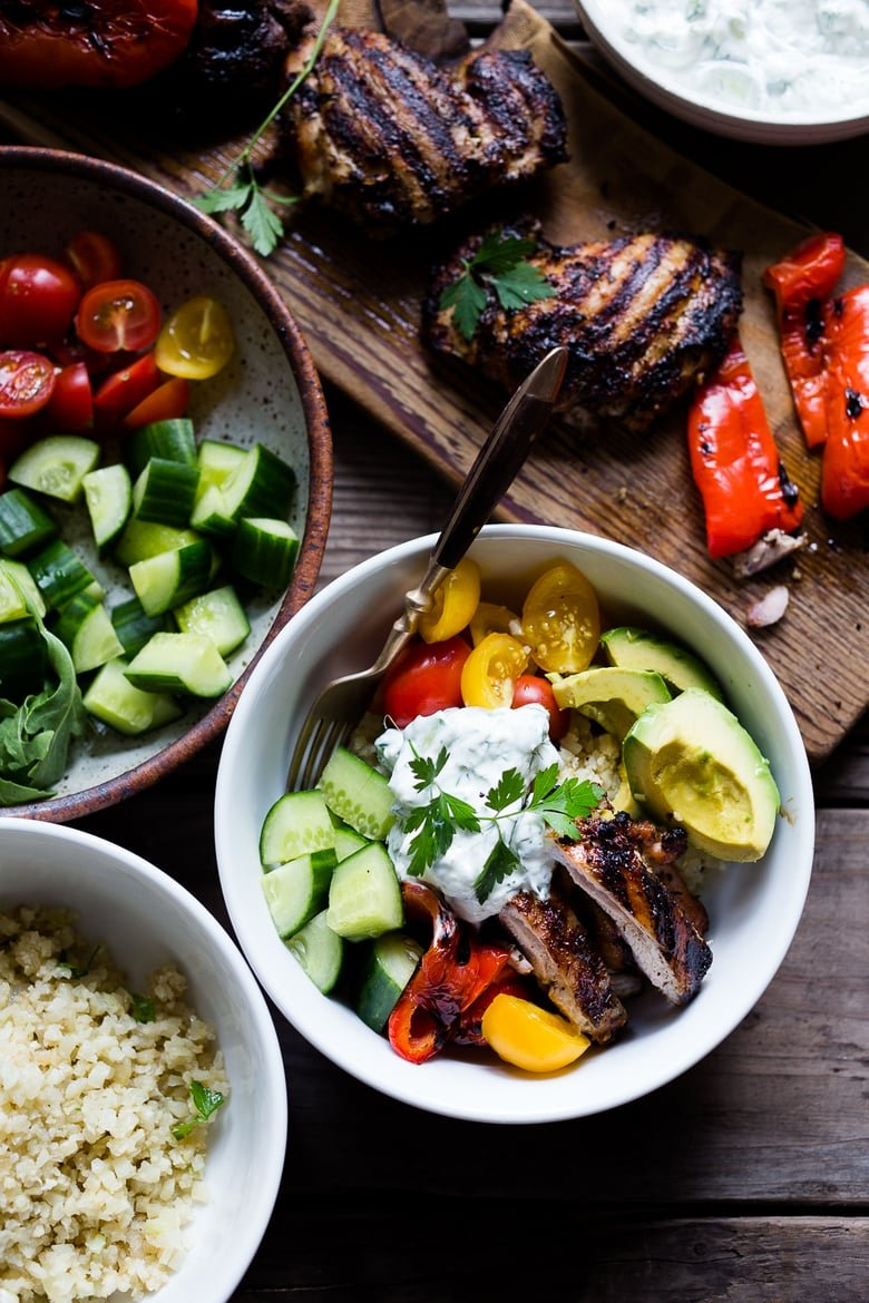 A simple tasty recipe for Grilled Greek Souvlaki Bowl with Cauliflower Rice, flavorful Cucumber Yogurt Sauce and fresh summer vegetables. | www.feastingathome.com