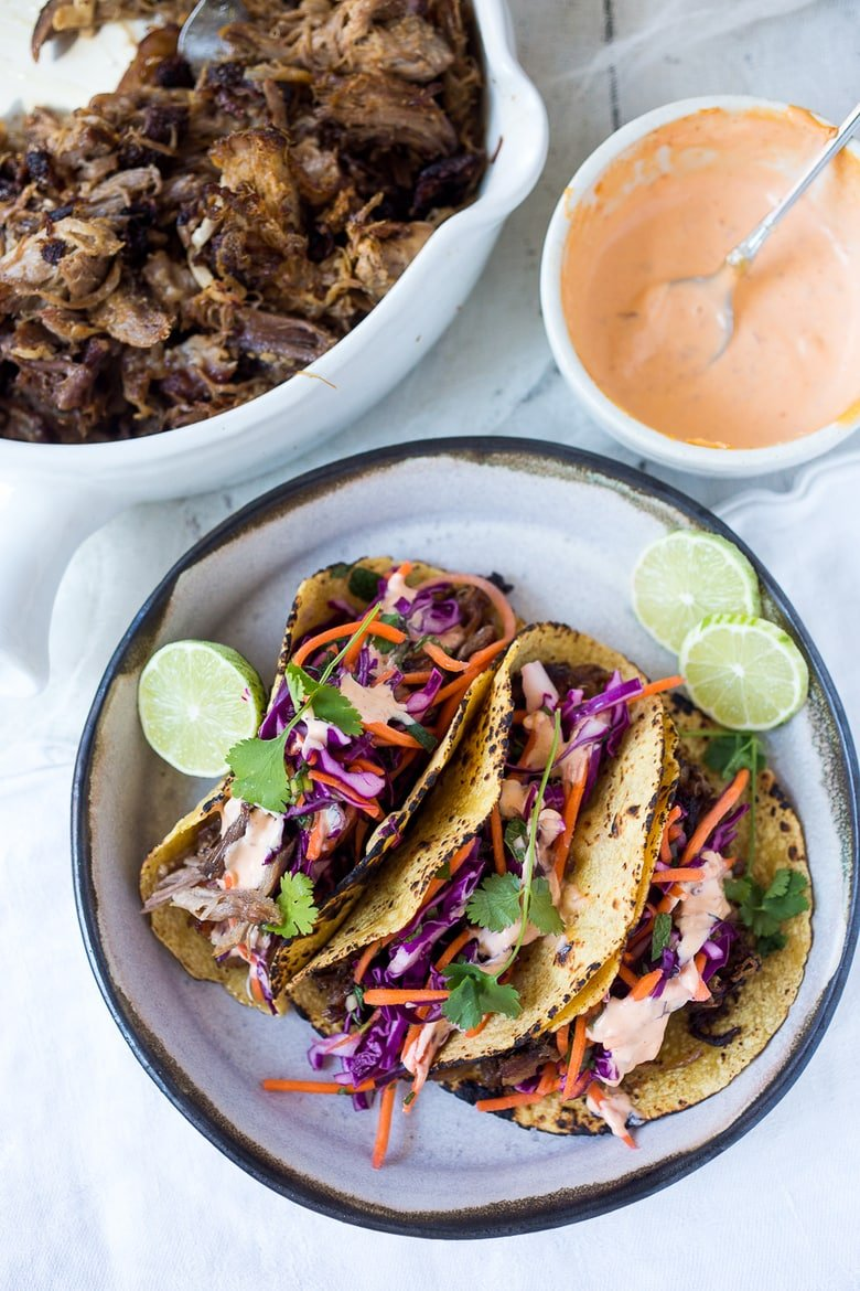Delicious slow-roasted, Pulled Pork Tacos are rubbed with flavorful Five Spice seasoning and served with Asian Slaw and a Spicy Sriracha Mayo.  A flavorful Asian twist on pulled pork tacos! #pulledporktacos #5spice #tacos