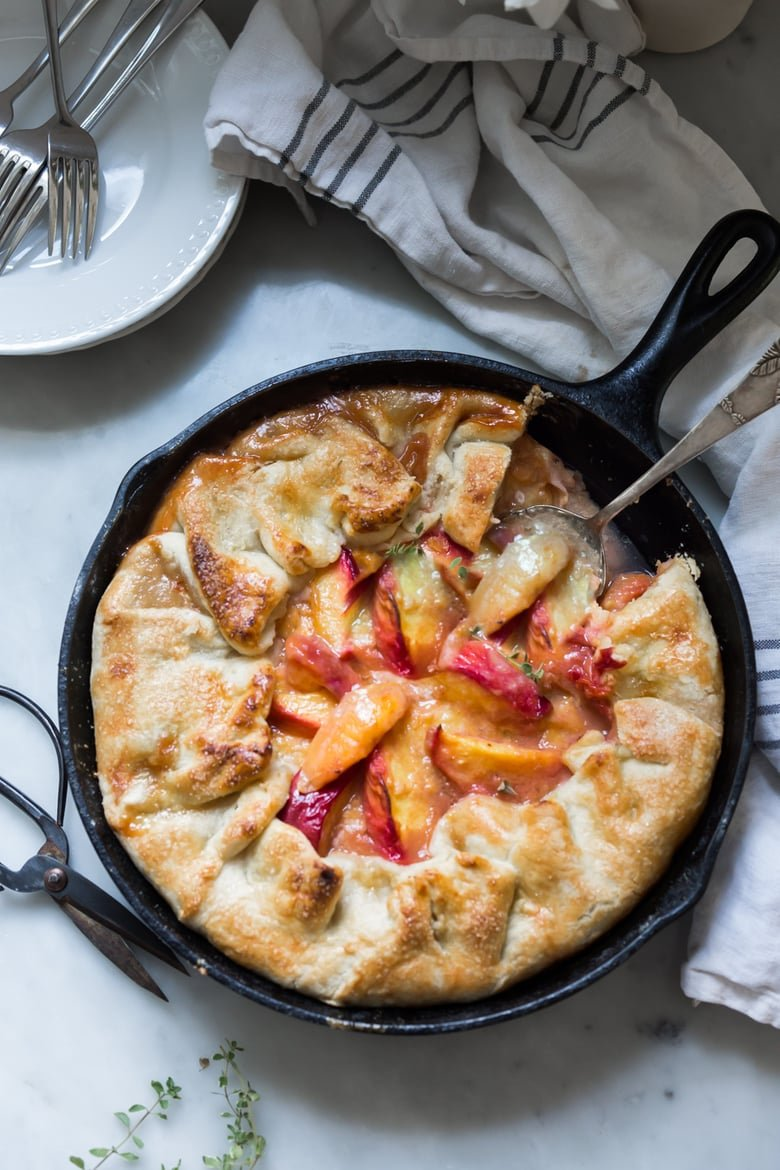 An old fashioned, Farm Style Peach Galette baked in a skillet. A simple, easy and fast recipe that comes out perfect every time! | www.feastingathome.com