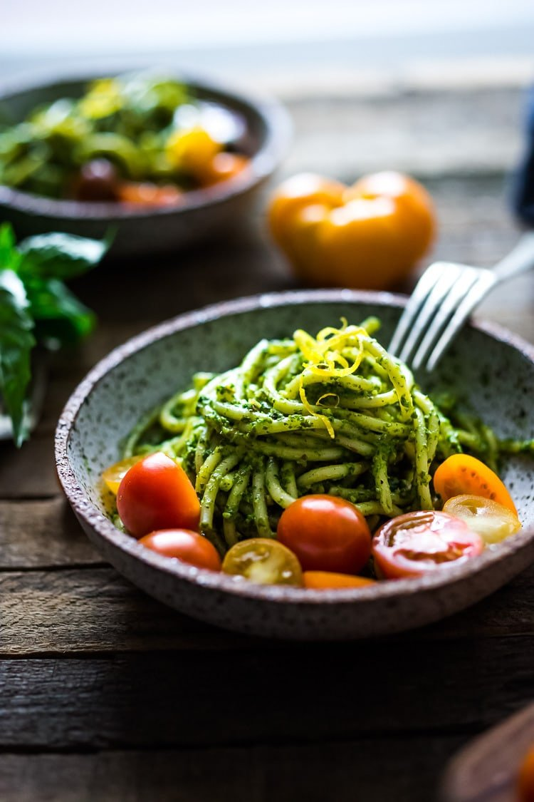 Bucatini Pasta with Arugula Pesto and Heirloom Tomatoes. A fast and flavorful weeknight dinner recipe. This Healthy pasta is Vegan! #bucatini #bucatinipasta #pastawithpesto #arugulapesto www.feastingathome.com