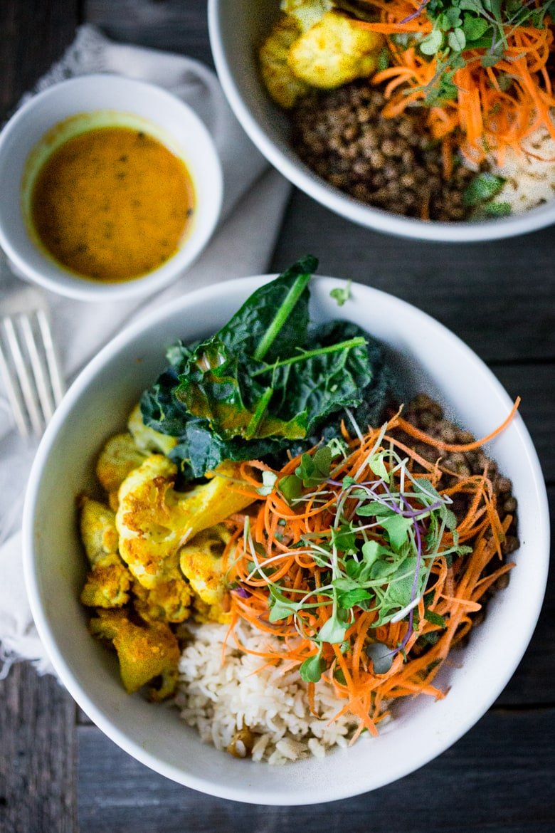 Nourish Bowl with Curried Cauliflower, lentils, brown rice and Kale is topped with a tangled Carrot Slaw and drizzled with a light and healing Turmeric Vinaigrette. Nurturing and soothing, this bowl is a gift to the tired, overindulged body.