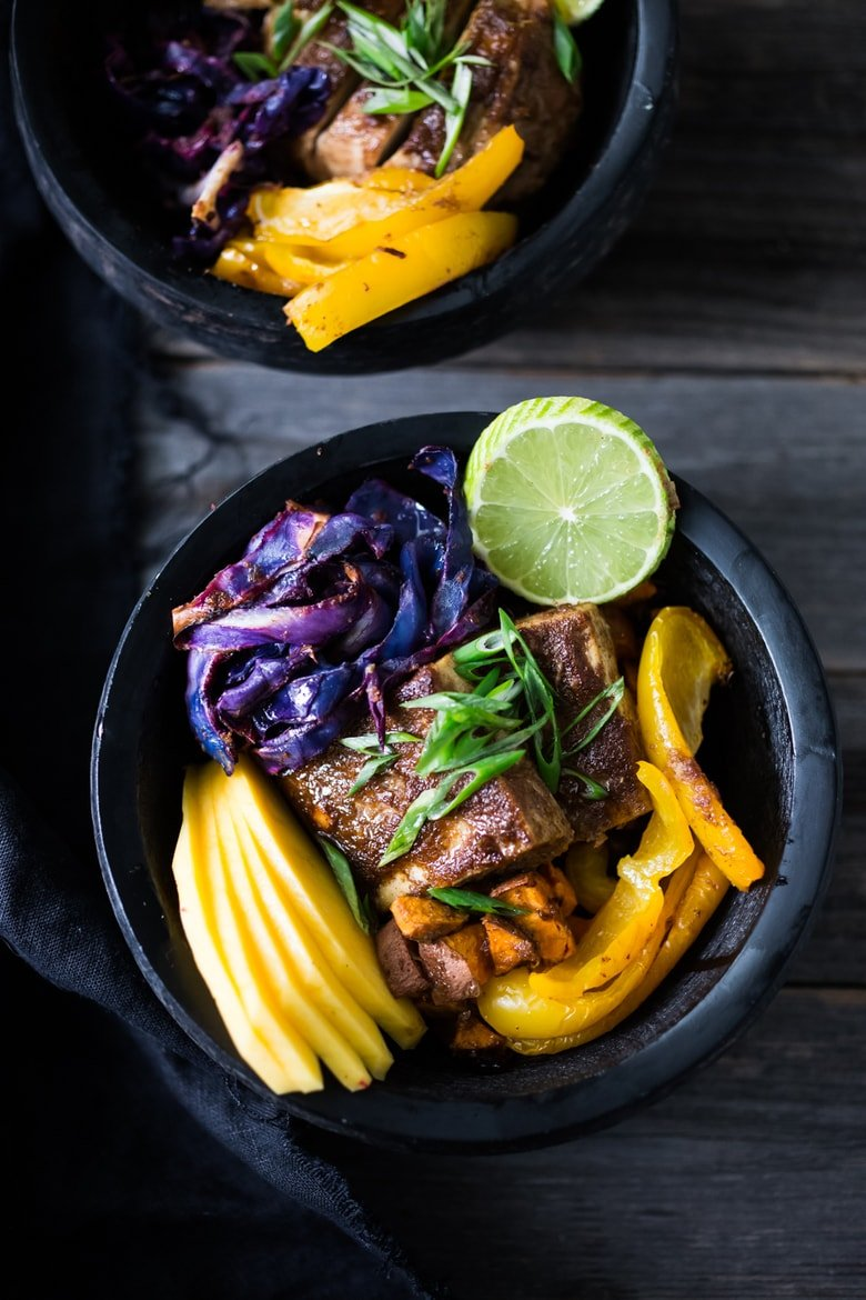 Caribbean-Style Voodoo Bowl- Roasted cabbage, sweet potatoes and tofu, over a bed of seasoned blackbeans with fresh mango and lime! | #veganbowl #cleaneating #eatclean #vegan #plantbased #buddhabowl #healthybowl #sheetpandinner www.feastingathome.com