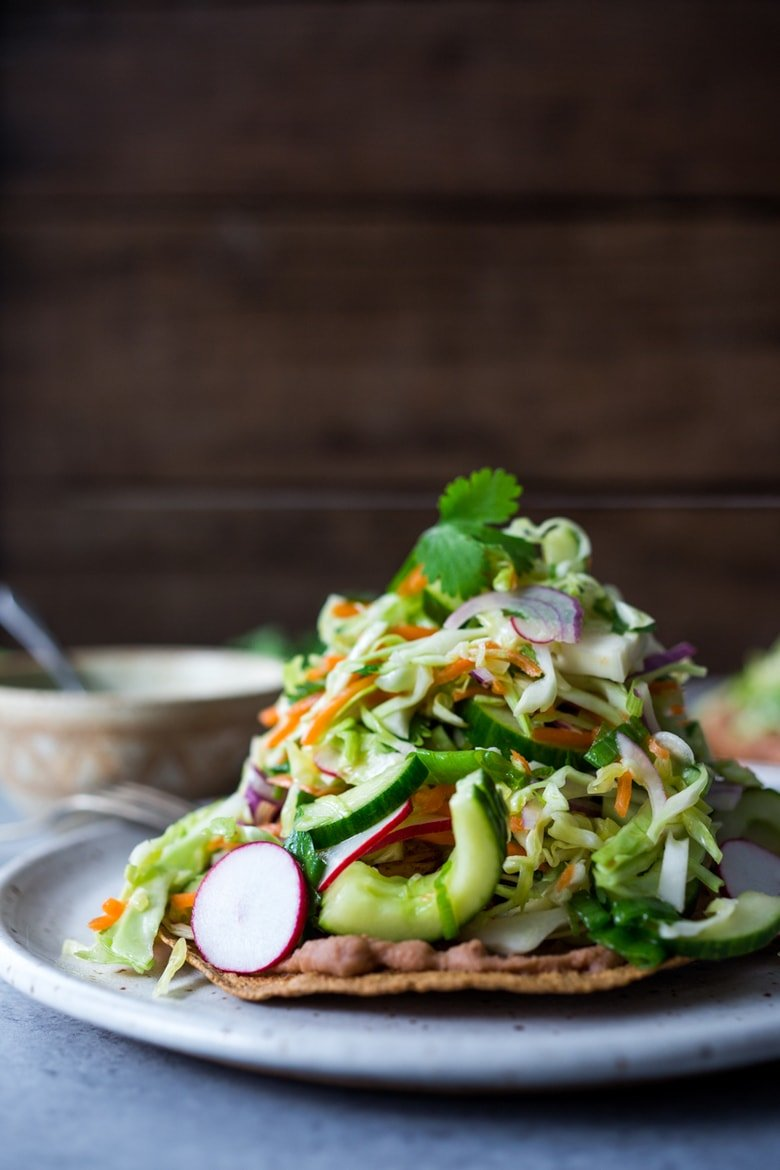 40 Mouthwatering Vegan Dinners!| Tlayudas Recipe! Traditional Oaxacan street food, tlayudas are a cross between a tostada and a pizza, made with a crispy tortilla, topped with refried beans, cheese (optional) cabbage slaw, avocado and cilantro. This healthy version is vegan and GF adaptable! | #tlayudas #tostadas #mexicanpizza #vegan #oaxacanfood #mexicanstreetfood #veganmexican #healthymexicanrecipes | www.feastingathome.com