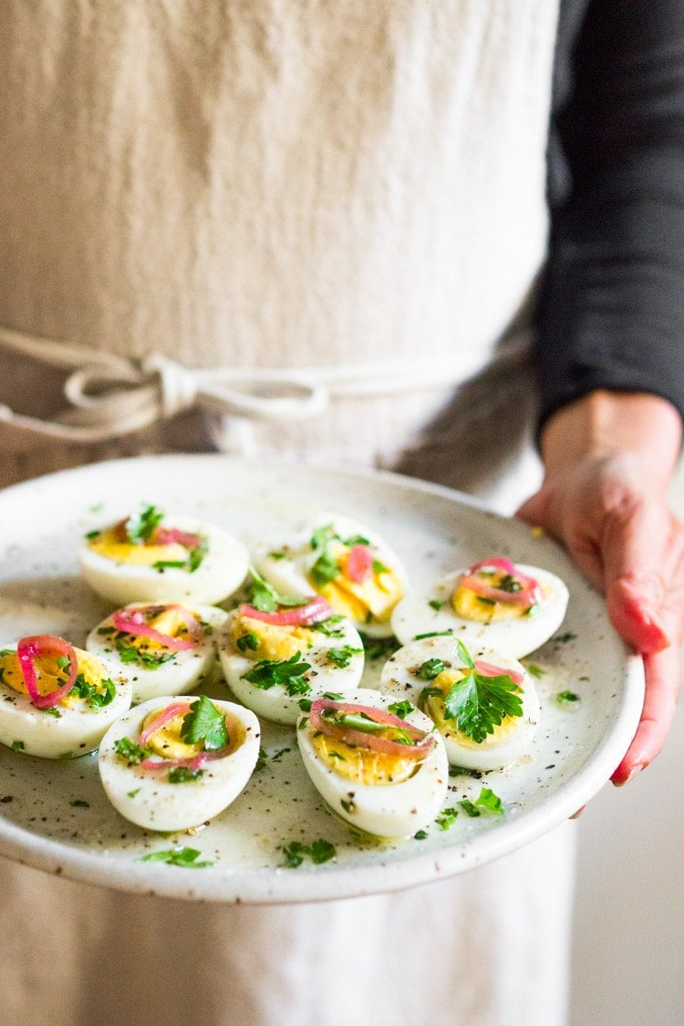 Quick and Easy Hard boiled eggs with olive oil, fresh herbs and pickled shallots, a simple, make ahead brunch recipe that is  perfect for gatherings and potlucks. Think of these like deviled eggs but in ½ the time! #deviledeggs #hardboiledeggs #boiledeggs #brunchrecipe