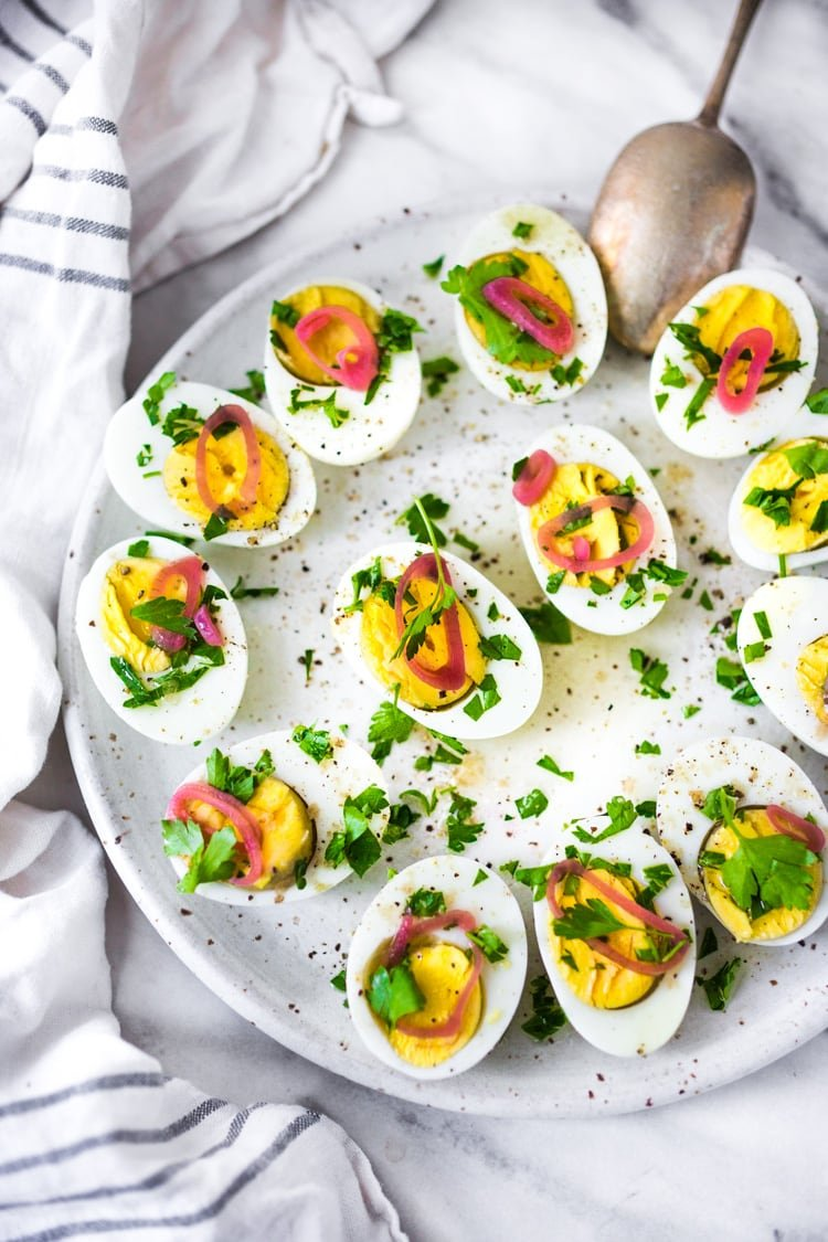 Quick and Easy Hard boiled eggs with olive oil, fresh herbs and pickled shallots, a simple, make ahead brunch recipe that is perfect for gatherings and potlucks. Think of these like deviled eggs but in½ the time!#deviledeggs #hardboiledeggs #boiledeggs #brunchrecipe