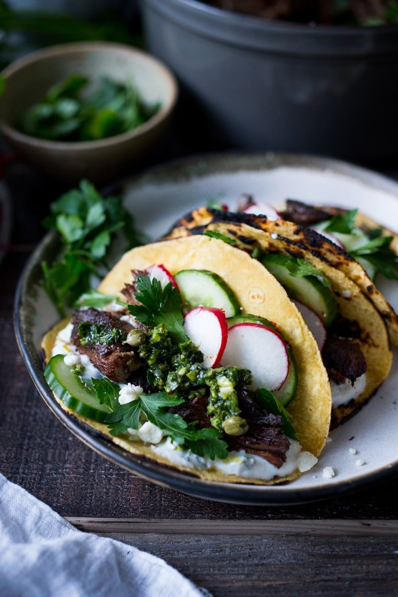 Greek Lamb Tacos with Tzatziki Sauce, cucumber and radishes. A Made with tender, falling off the bone, slow-roasted Lamb shoulder. Delicious flavors! #lamb #lambtacos #lambshoulder #slowroasted #braisedlamb www.feastingathome.com