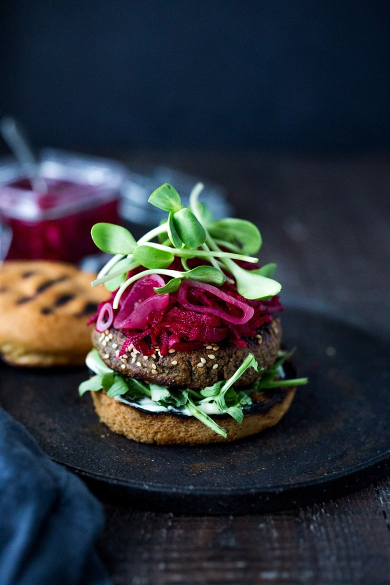 Sprouted Lentil Burgers- made with walnuts and brown rice, these grillable, vegan and gluten-free adaptable. Super healthy and delicious, packed with living nutrients! Topped with picked beets. | www.feastingathome.com