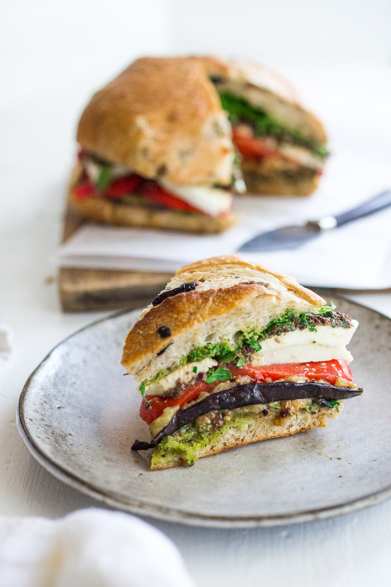 Grilled Eggplant Muffuletta Sandwich with Pesto, roasted peppers, olive tapenade and fresh mozzarella. All the flavors of summer in one bite! | www.feastingathome.com