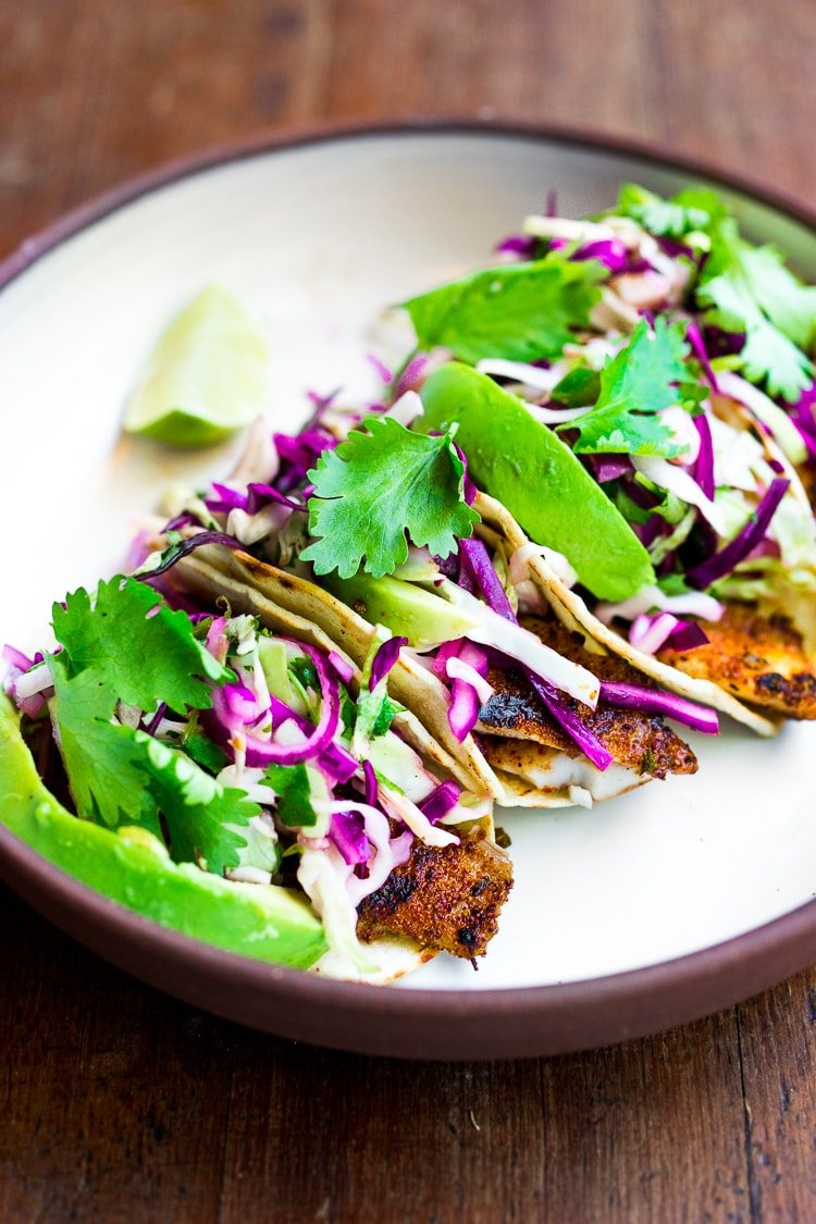 Quick & Easy Fish Tacos topped with Cilantro Lime Cabbage Slaw that can be made using a grill, stove top or oven! Vegan & gluten-free adaptable! A fast and healthy dinner that comes together in under 30 minutes. | #feastingathome #slaw #fishtacos #tacos #grilled #grilling #tacoslaw #cabbageslaw #tofutacos #vegantacos #bakedtacos ##healthytacos #mexicanslaw #mexicanslaw