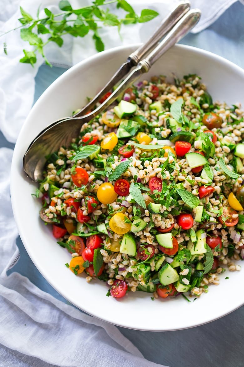 A simple delicious recipe for Farro Tabbouleh Salad loaded up with summer veggies, herbs and simple lemon dressing. Vegan! | www.feastingathome.com