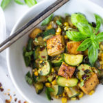 A fast and healthy dinner -Zucchini, Corn and Basil Skillet topped with your choice of shrimp, tofu or chicken. Simple and adaptable. Vegan, Gluten-free! | www.feastingathome.com