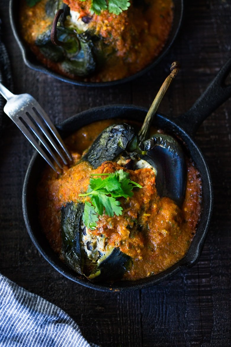 A healthy, vegan adaptable,RoastedChiles Rellenos Recipe - that is lightened up with the addition ofblack beans. Simplified by roasting (instead of frying) the peppers with the Salsa Ranchero Sauce ingredients - all baked together on one sheet-pan - saving a step! #chiliesrancheros