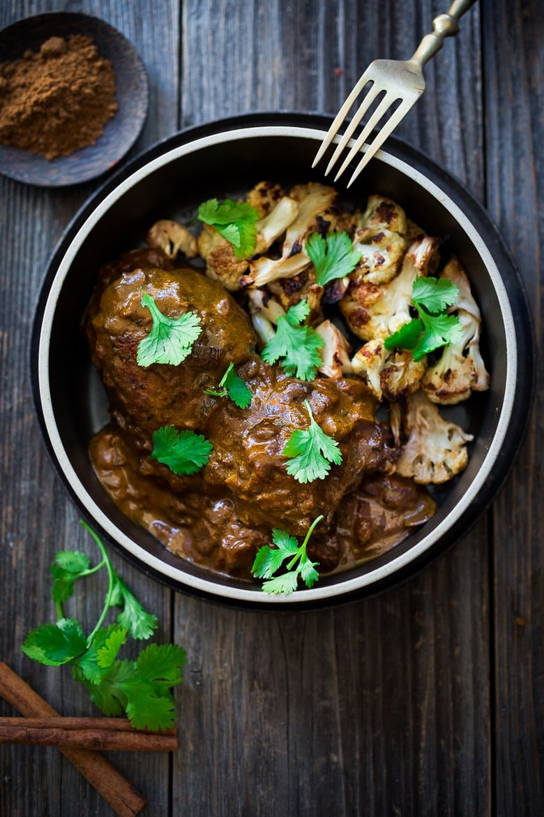 Indian Butter Chicken (or Cauliflower) in the most flavorful Tomato Ginger Coconut Curry Sauce! Serve over roasted cauliflower or brown basmati rice- a flavorful meal that is vegan adaptable! | www.feastingathome.com