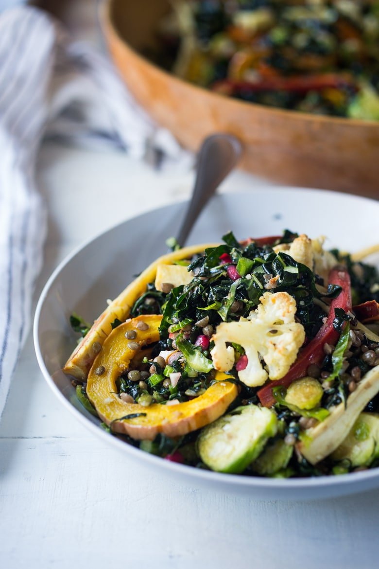 A hearty, healthy Roasted Fall Vegetable Salad with Maple Curry Vinaigrette on a bed of shredded kale and brussel sprouts. Vegan and GF. | www.feastingathome.com