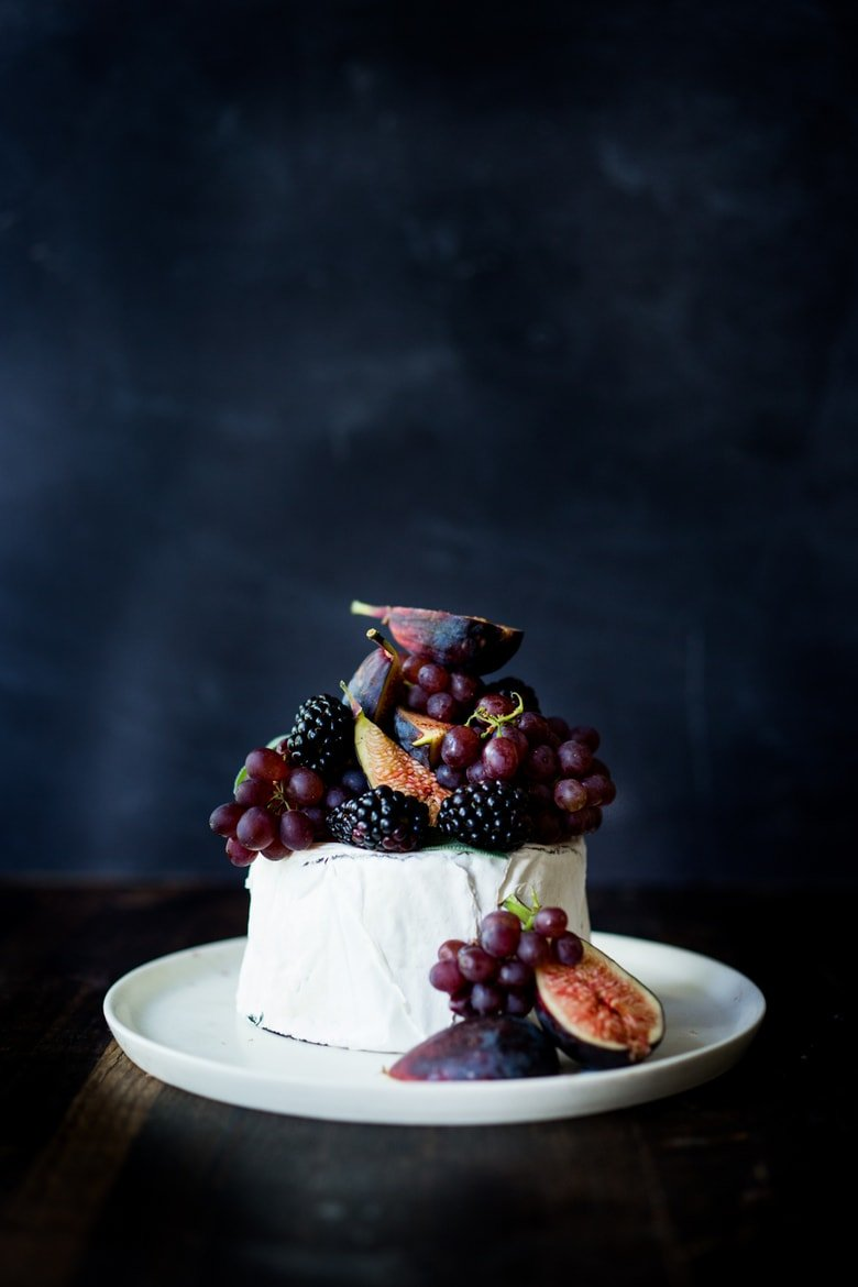 Simple, beautiful Brie Cake topped with fresh berries, figs and grapes, drizzled with honey and served with seeded crackers -  an easy, festive appetizer or dessert, perfect for celebrations and gatherings.  | www.feastingathome.com