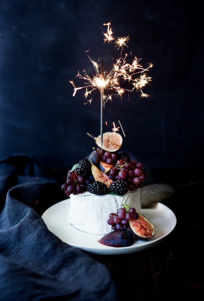 A simple Brie Cake topped with fresh berries, figs and grapes, drizzled with honey and served with seeded crackers -  an easy, festive appetizer or dessert, perfect for parties, celebrations and gatherings.  | #briecake #newyearseve #partyappetizers #appetizers www.feastingathome.com