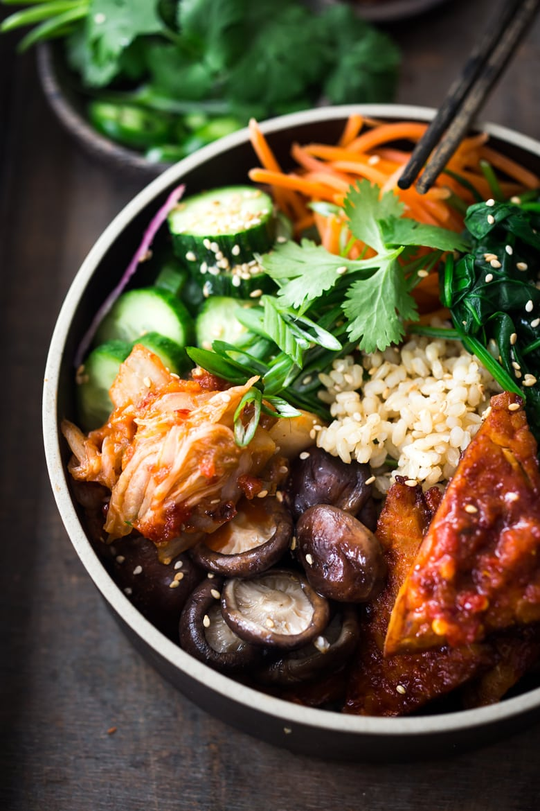 Vegan Seoul Bowl! This Korean -inspired bowl is made with Gochujang baked Tempeh, steamed veggies, kimchi and pickled cucumbers- a healthy vegan version of Bibimbap! #veganbowl #buddhabowls #vegan #plantbased #eatclean #cleaneating #detoxrecipes #detox #plantbased #healthybowls #bibimbap #veganbibimbap