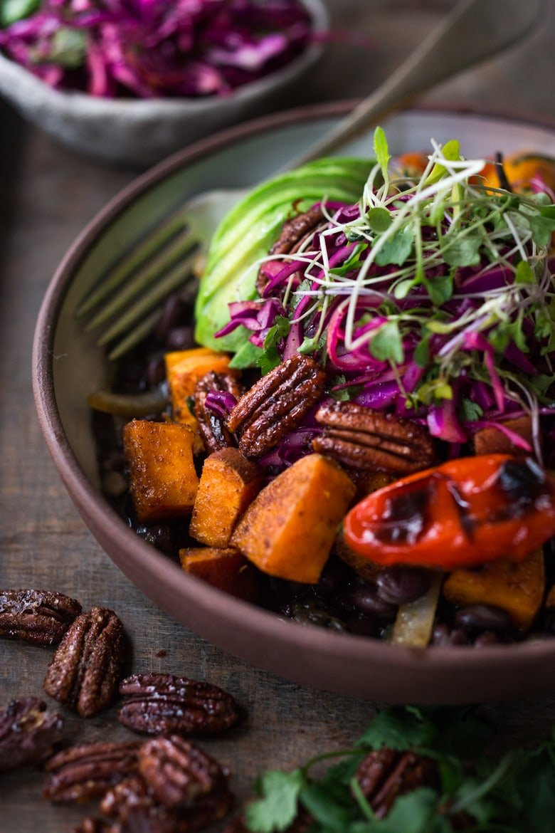 Here's a healthy, flavorful Mexican -style Oaxacan Bowl with roasted chipotle sweet potatoes and sweet peppers over a bed of warm seasoned black beans. It's topped with a crunchy cabbage slaw, avocado and my favorite thing ever, toasted Chipotle Maple Pecans. Vegan and grain-free, hands down, this bowl is my new favorite!