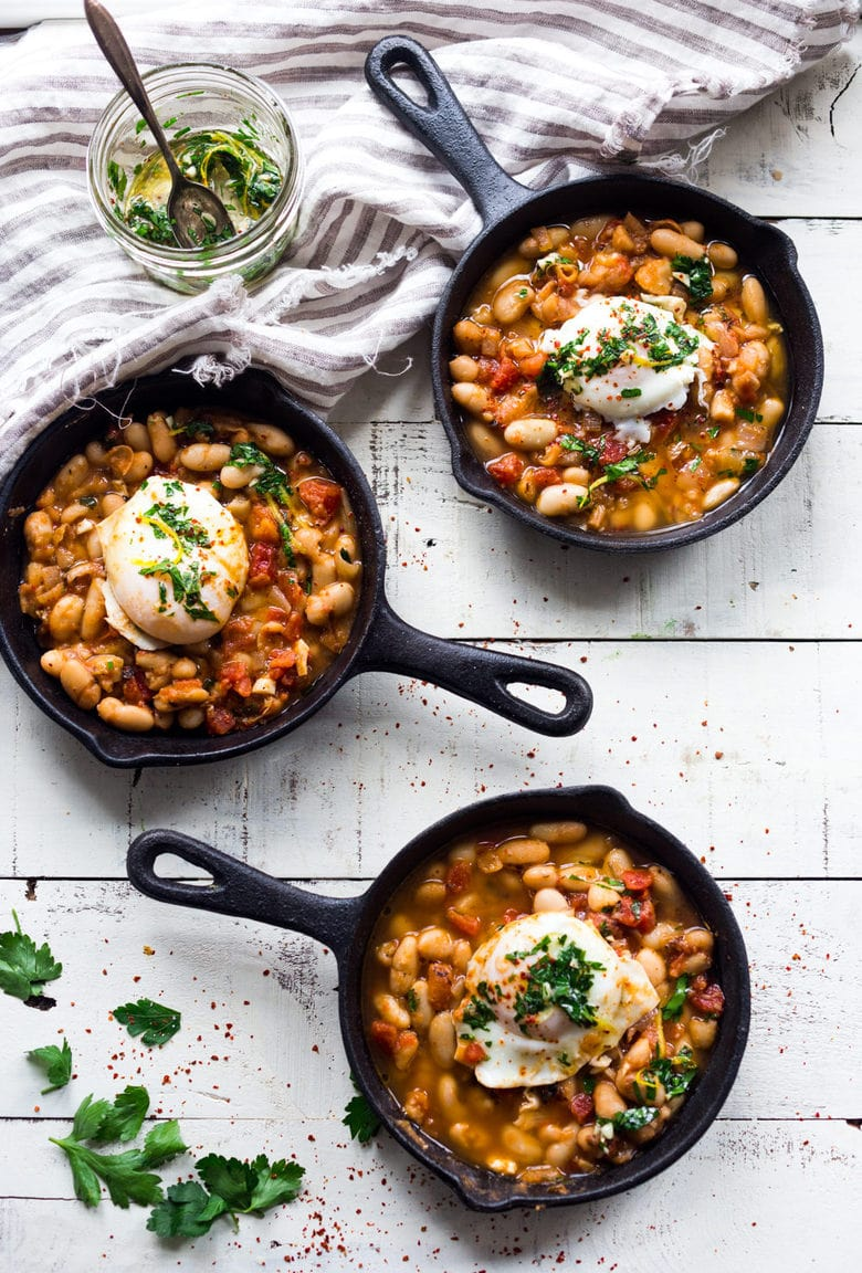Tuscan Farmers Breakfast! Gently simmered eggs over a flavorful cannellini bean stew topped an herby gremolita sauce. Add Italian sausage or keep it vegetarian. Healthy and tasty!